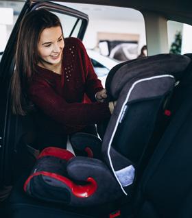 mujer-instalando-una-sillita-de-seguridad-en-coche