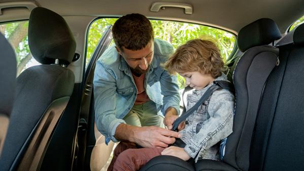 padre-poniendo-cinturon-en-la-sillita-para-niños-en-coche