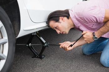 hombre-elevando-el-coche-con-gato-para-cambiar-rueda