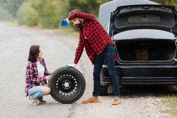 pareja-cambiando-la-rueda-del-coche